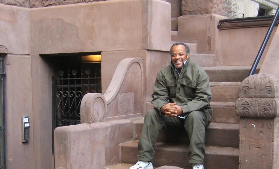 Smiling man sitting on apartment. steps