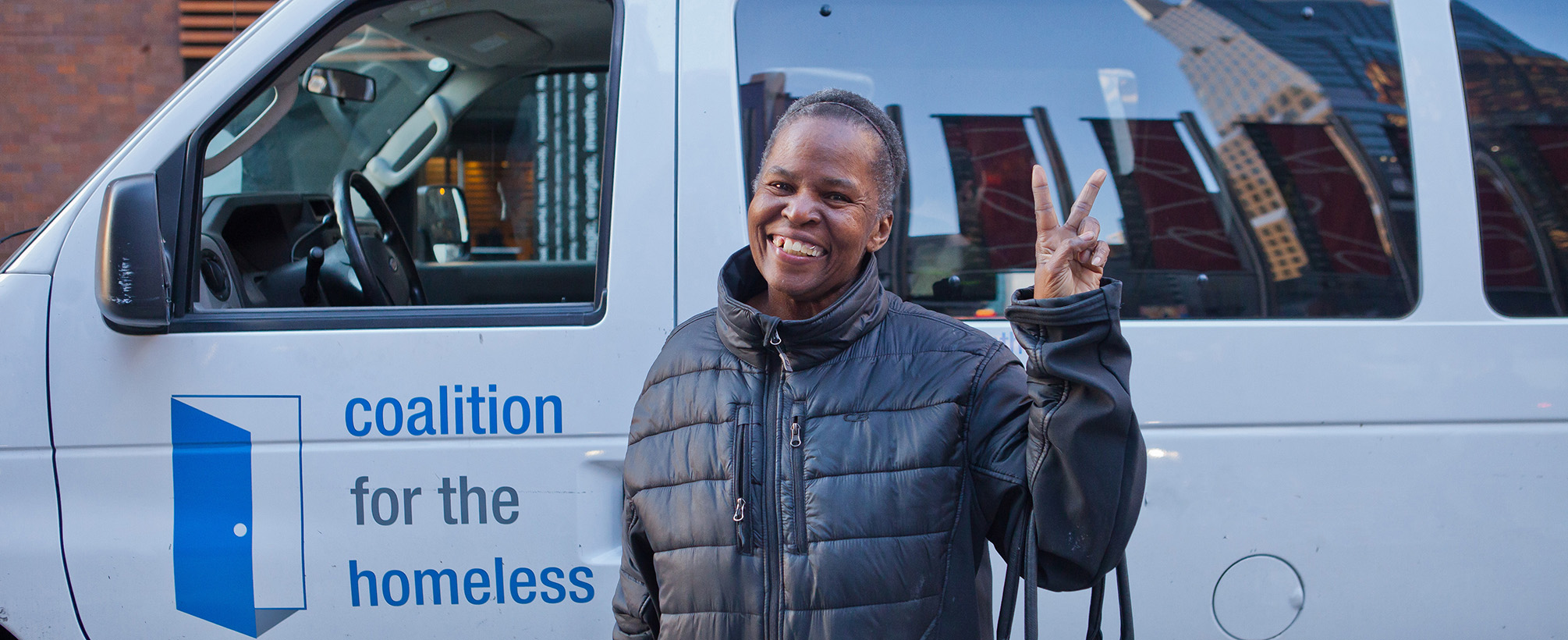 Woman in black coat, standing in front of GCFP van, smiling and holding peace sign