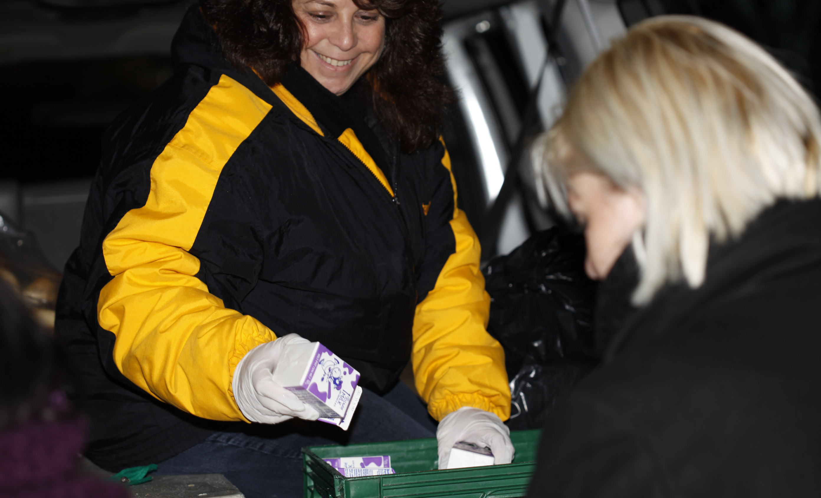 Smiling woman in black and yellow coat handing out small cartons of milk