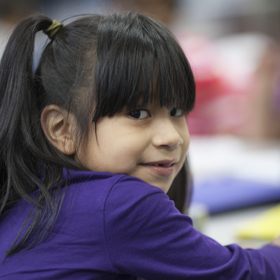 Young girl with pigtails and a purple shirt.