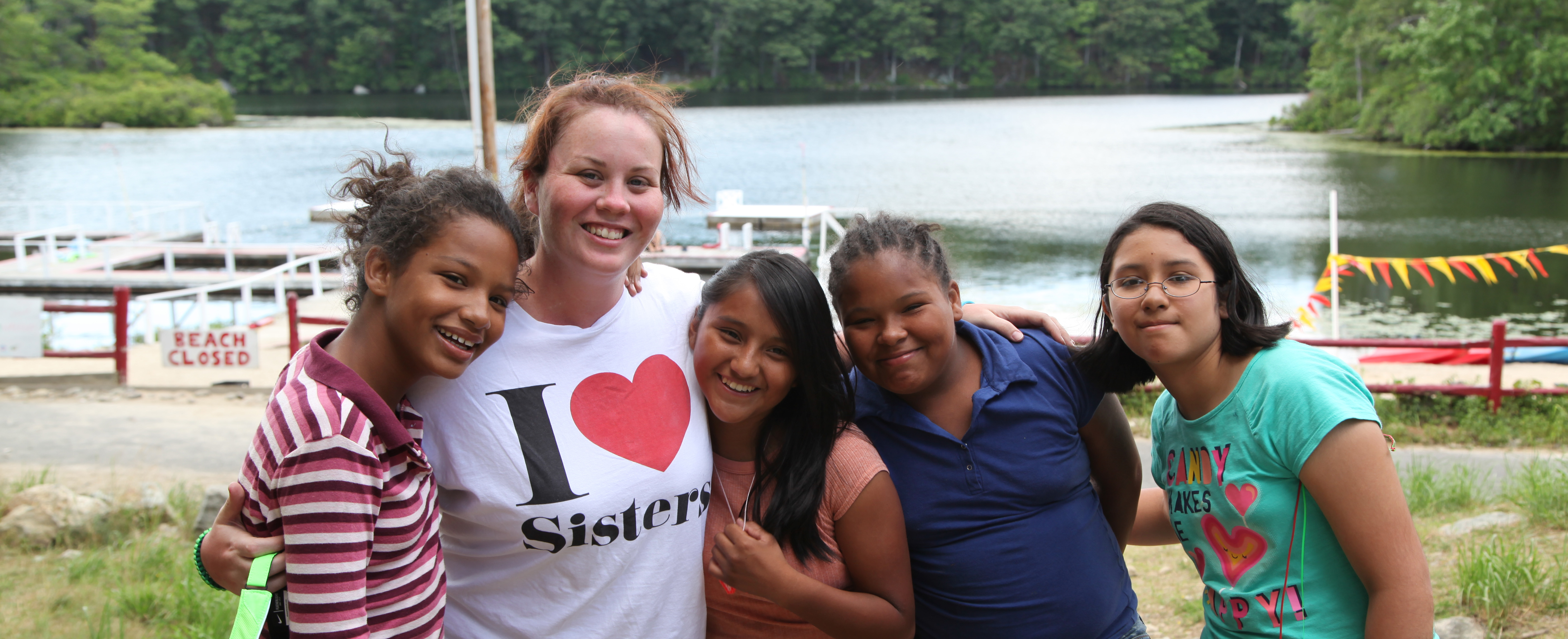 Female camp counselor smiling with a group of girls in front of the lake.