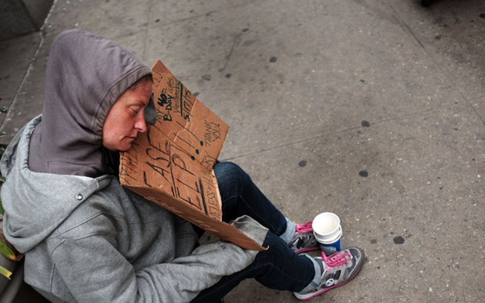 NEW YORK, NY - MAY 18:  A homeless woman rests while panhandling along Eighth Avenue in Manhattan on May 18, 2015 in New York City. As many parts of once seedy New York  City have been transformed into family and shopping friendly environments, 8th Avenue near the Port Authority bus station is one of the last hold-outs to old gritty Manhattan. Last week a man was shot by police after he attacked numerous people with a hammer along a stretch of the street. There is a high police presence along the street and fights and arrests for vagrancy are common.  (Photo by Spencer Platt/Getty Images)
