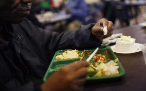 A man eats lunch at the Capuchin Soup Kitchen, where hundreds of people receive food and supplies everyday, in Detroit, Michigan, December 9, 2008. REUTERS/Carlos Barria (UNITED STATES) - RTR25A82