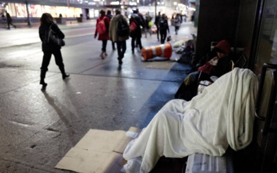 Person sleeping on sidewalk wrapped in blanket