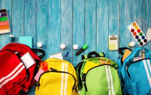 Red, yellow, green, and blue backpacks and various school supplies are set on a blue background.
