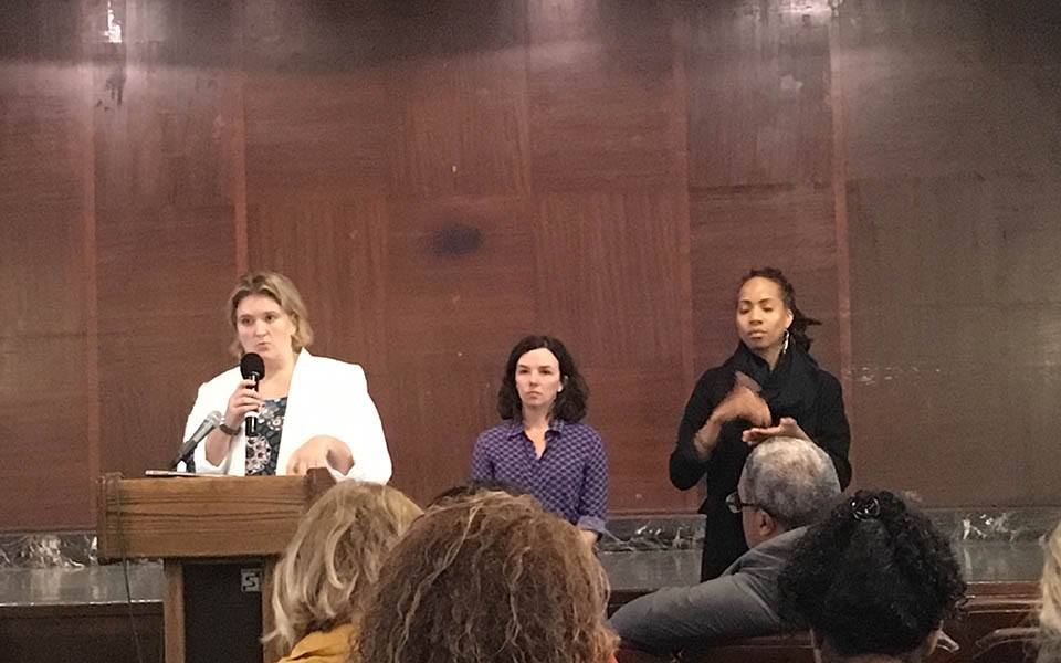 Legal Aid Society's Beth Hofmeister and CFH Policy Director Giselle Routhier presenting testimony at the front of a room with brown paneled walls. A sign language interpreter stands to the right.