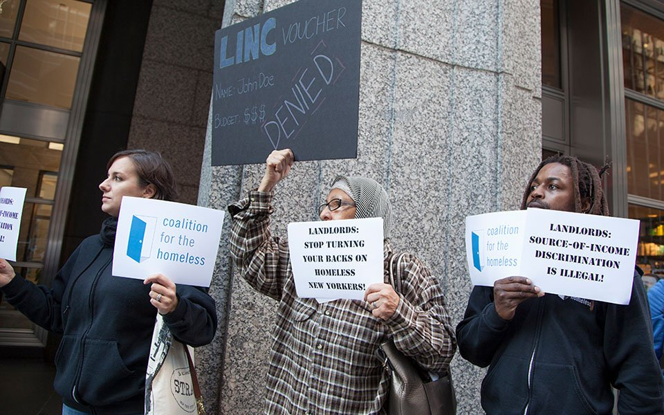 Group of three protesters with Coalition signs and signs regarding LINC voucher discrimination.