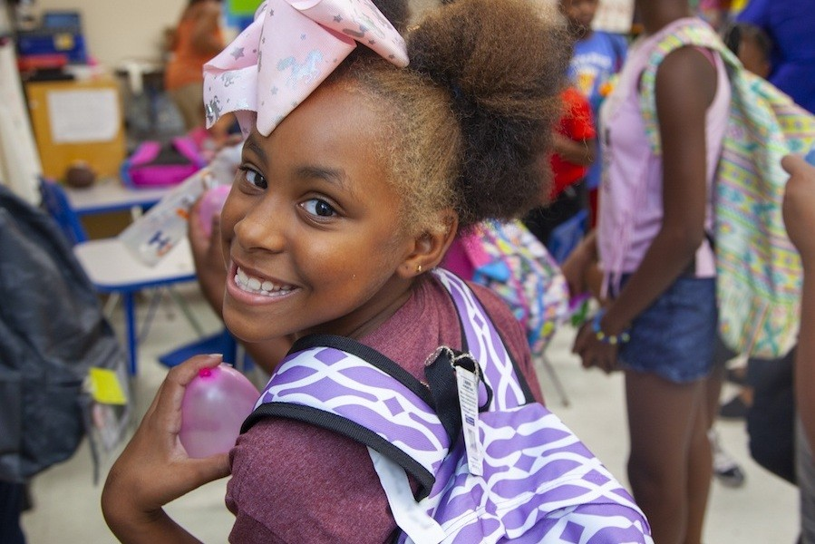 Smiling girl holding a backpack