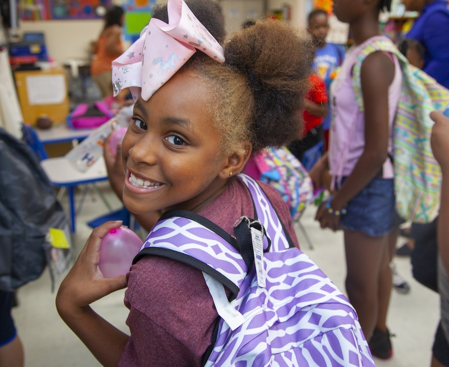 Girl holding backpack and smiling