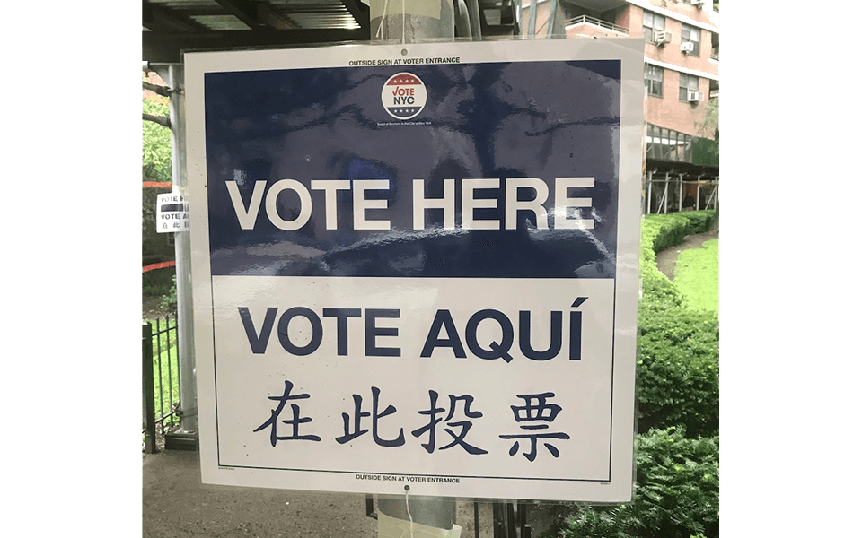 """Polling location sign. Text reads """"Vote here"""" in English, Spanish, and Chinese"""