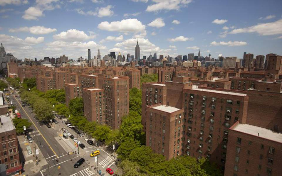 Brick apartment buildings with the New York City skyline in the background