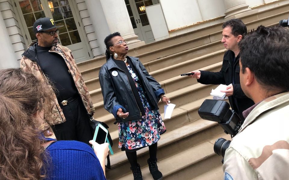 Ms. Flowers speaking to reporters on the steps of City Hall