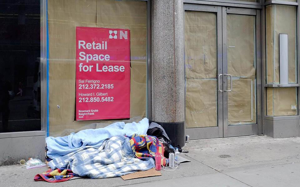 A person sleeps on the sidewalk in front of a vacant storefront.