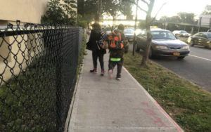 Two children with backpacks walk on the sidewalk of a tree-lined street.