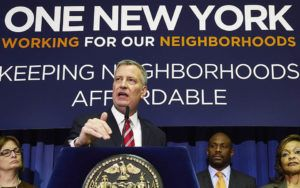 """Mayor de Blasio speaks at a podium, with a banner reading """"One New York"""" behind him."""