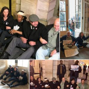 Protesters sit down at City Hall with arms linked