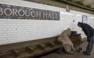 A homeless man sits under a blanket in a subway station.