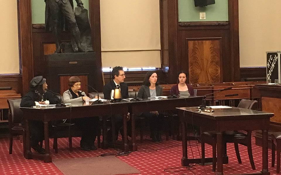 Coalition for the Homeless Policy Director Giselle Routhier and four other people sit at a table to testify at New York City Hall