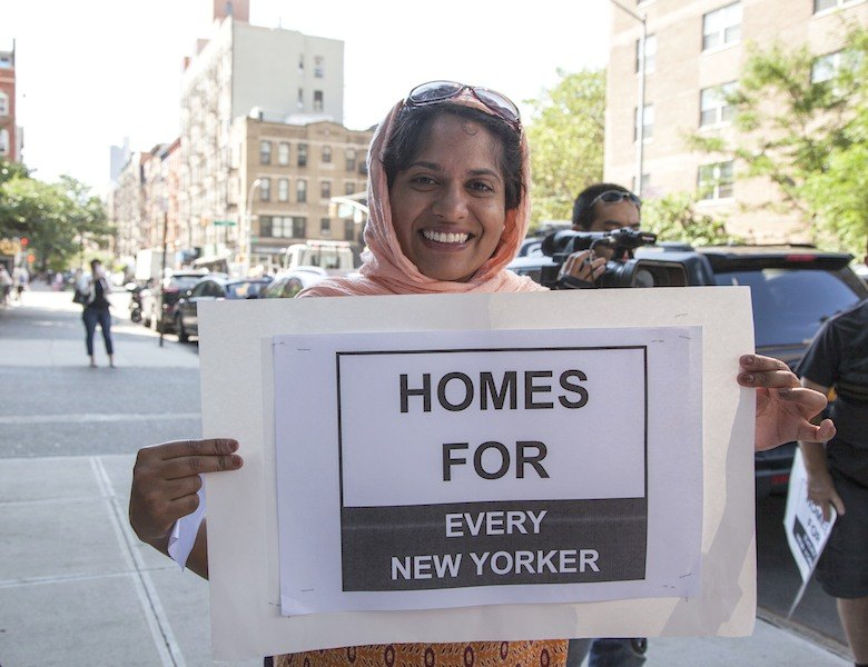 Woman holding a sign that says homes for every New Yorker