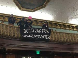 """Activists in City Hall holding banner reading """"Build 24K for Homeless NYers"""""""