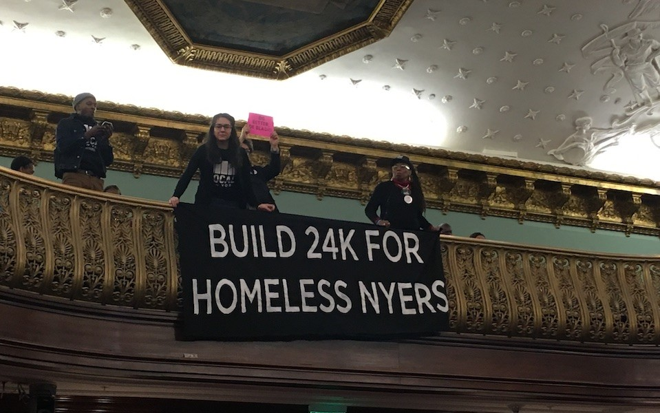 Activists in City Hall holding banner reading