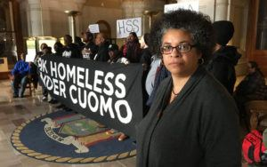 A woman stands in front of a group of protesters holding a banner that reads: 89k Homeless Under Cuomo