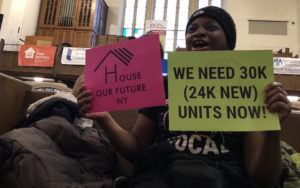 "Woman holding signs that say ""We Need 30K (24K New) Units Now"" and ""House Our Future NY"""