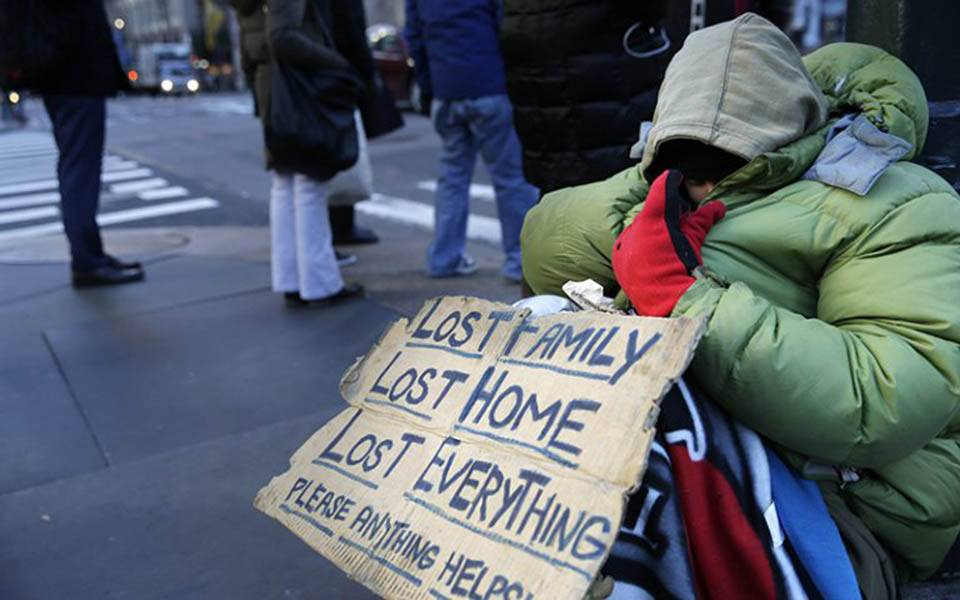 A homeless person with a sign sits on the sidewalk