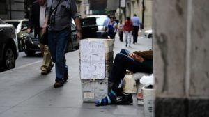 Person sitting on the sidewalk with a box