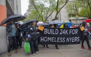 """Advocates marching while holding a sign that says """"Build 24K for Homeless NYers"""""""