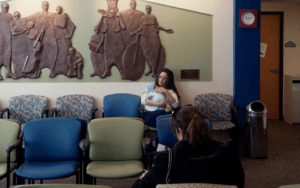 Woman sitting in a waiting room holding a child.