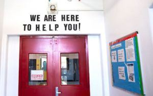 "A door inside the HELP shelter on Ward's Island. A sign reading ""We are here to HELP you."""