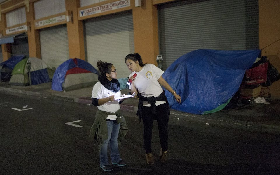 Two women talking on a street while holding flashlights and clipboards. A row of tents are set up behind them.