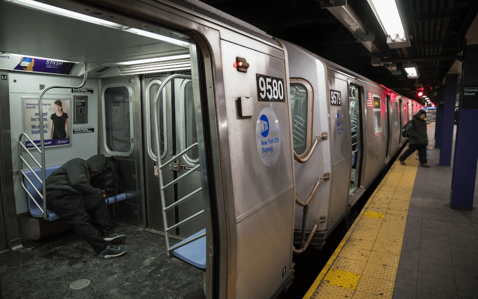 Subway car door open in station. A person wrapped in blankets seated inside.