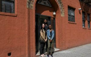 Three people stand outside a brick building