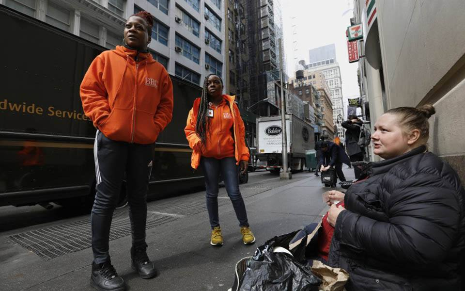 Two outreach workers speak with a homeless woman on the sidewalk