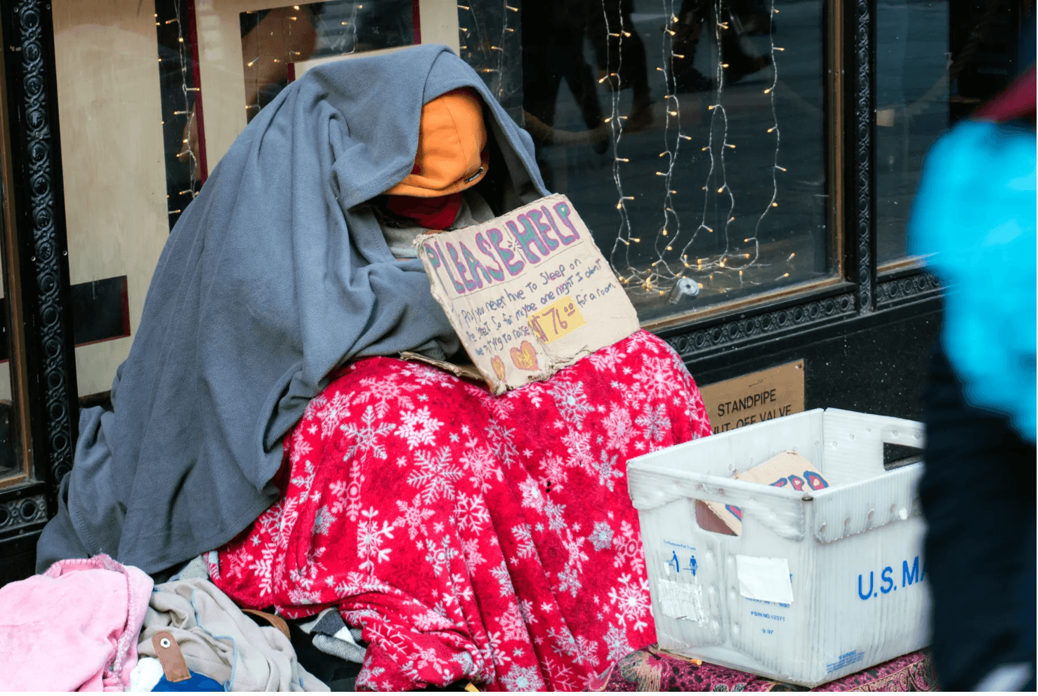 """Person wrapped in blankets sitting on the sidewalk with a sign reading """"Please help!"""""""