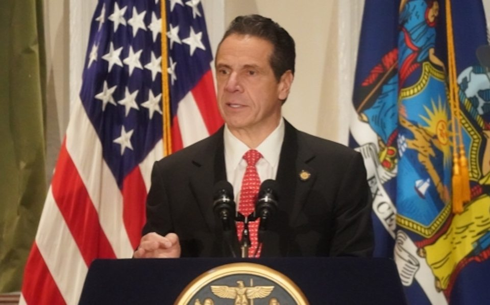 Governor Cuomo standing at a podium with the American and NY State flags in the background