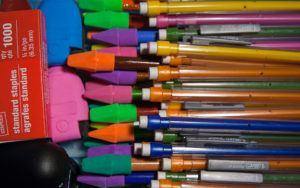 Colorful pencils, erasers, and a box of staples