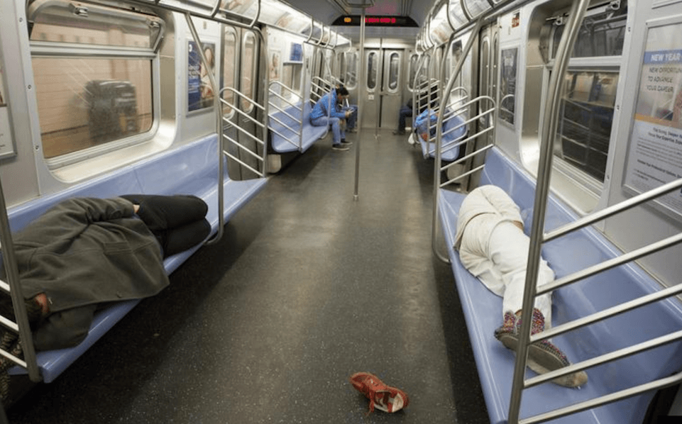 People sleeping on a mostly empty subway car.