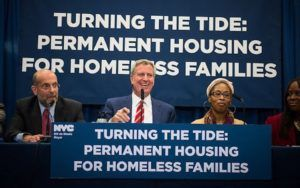 "Mayor Bill de Blasio giving a speech. Sign reads: ""Turning the Tide: Permanent Housing for Homeless Families"""