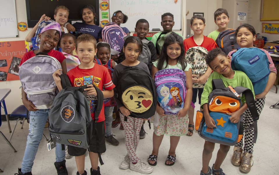 Kids posing with backpacks