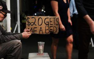 "Man holding a sign saying ""$20 gets me a bed"""