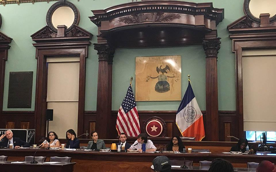 NYC Council Members and staff sit behind a desk with flags in the background