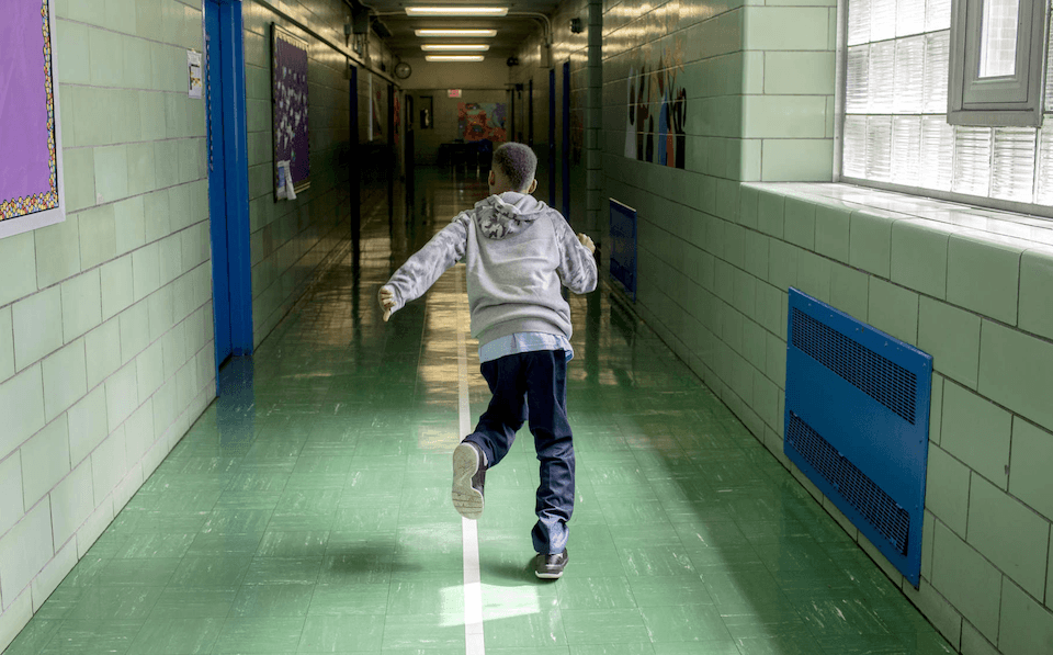 Boy running down the hall ways of a school