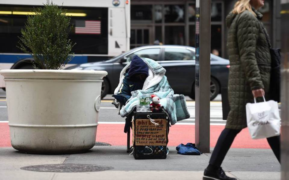 A homeless person on a city sidewalk