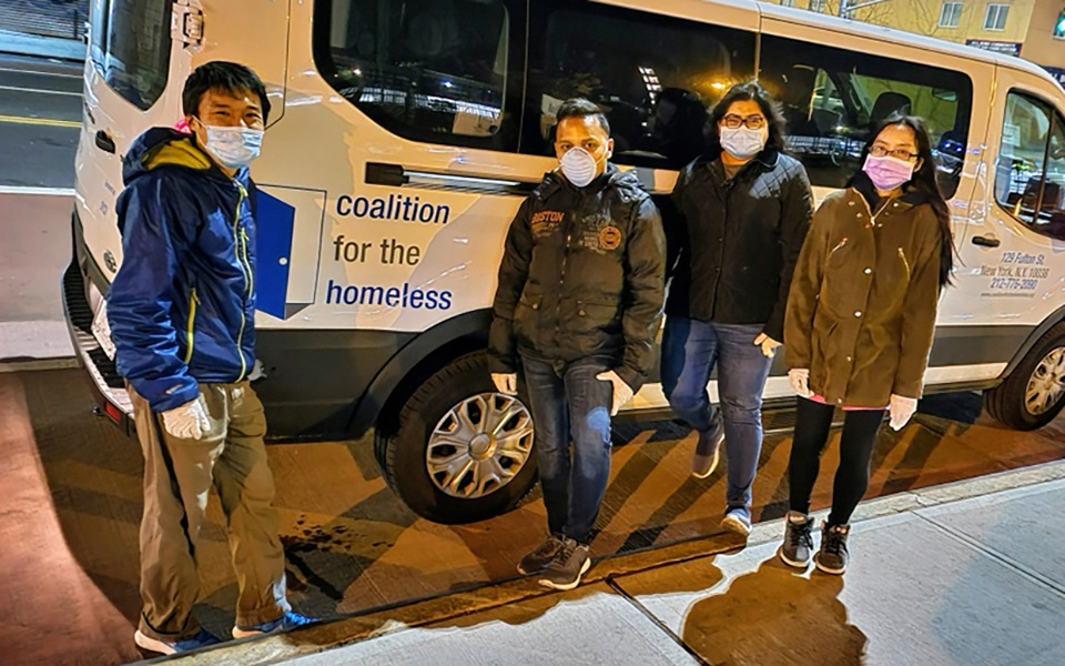 Group of people with face masks standing in front of the side of a van with logo Coalition for the Homeless