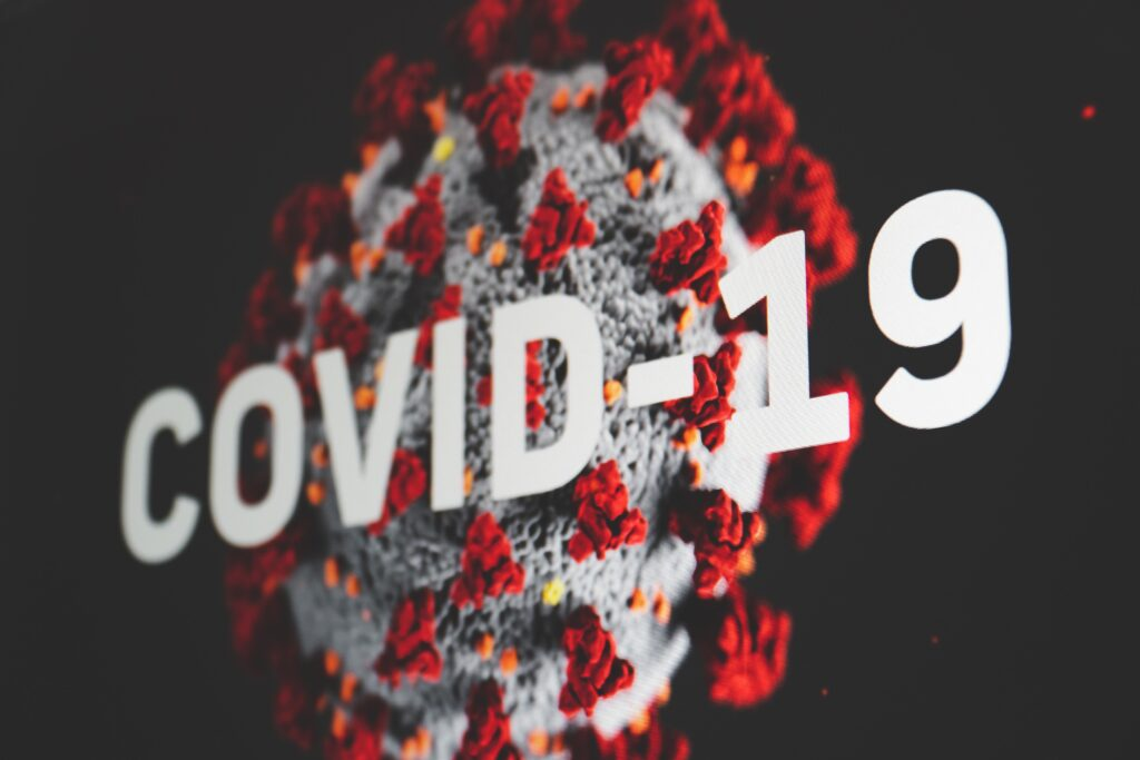 """A rendering of a virus cell with the words """"COVID-19"""" printed over top"""