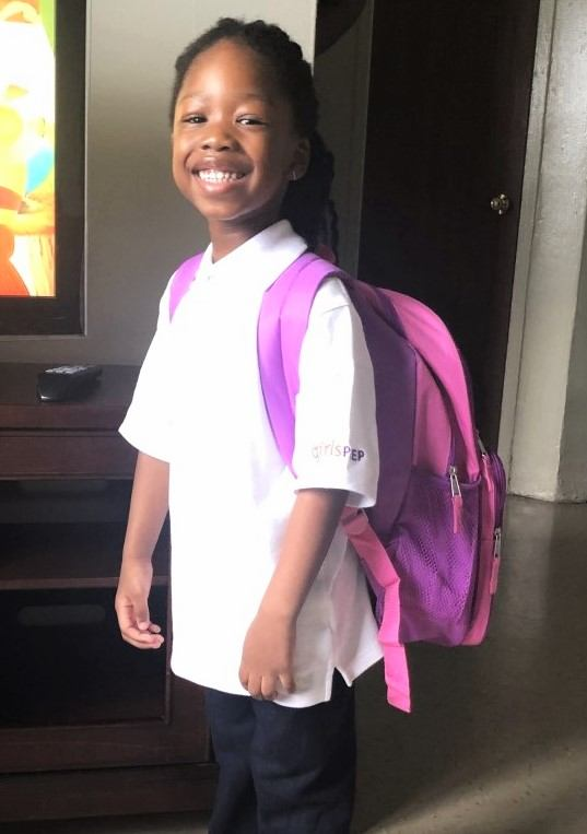A girl in school clothes stands with her body facing sideways showing off the pink backpack on her back, smiling broadly