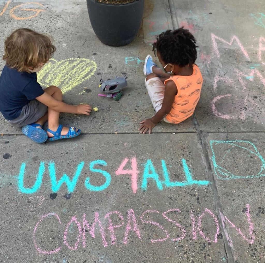 """Two kids sitting on pavement surrounded by chalk drawings, the words """"UWS4ALL"""" and """"CoMPASSION"""" are written by them"""